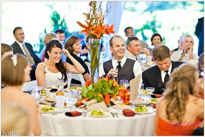 bride and groom sitting amongst guests